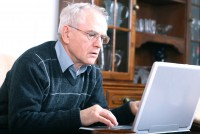 Senior man in front of his laptop